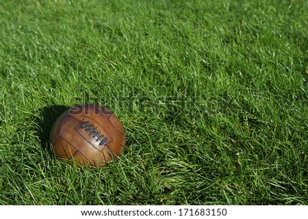 Vintage old brown football old-fashioned soccer ball sits in sunny green grass field