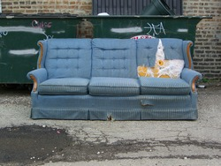 Vintage old grungy ripped abandoned couch left for garbage