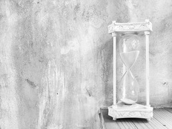 Vintage old hourglass on table with grunge concrete wall background.