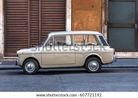 Vintage old italian car in front of orange building