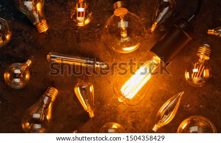 Vintage old light bulb glowing yellow on rough dark background surrounded by burnt out bulbs. Idea, creativity concept. #1504358429