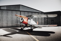 Vintage old plane in front of the hangar. Shadow on the ground.
