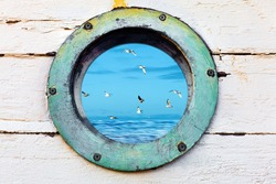 Vintage old porthole window with a view of the ocean and birds flying by.