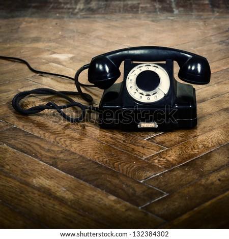 vintage old telephone, black retro phone is on the floor of used parquet