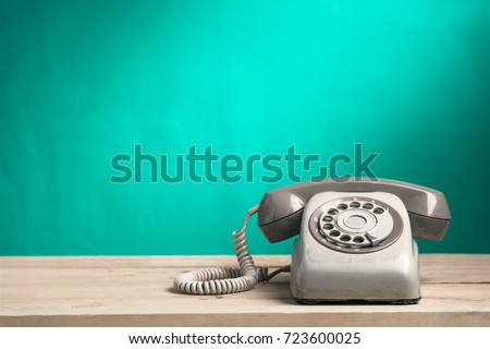 Vintage old telephone on wood table with turquoise wall background #723600025