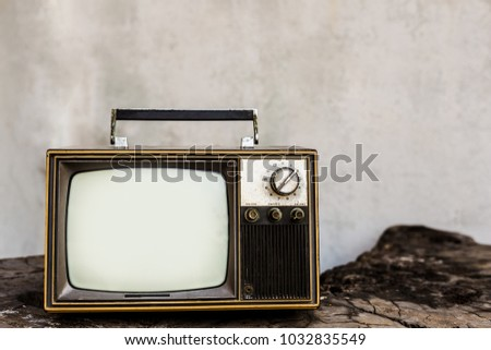Vintage old television on the wooden with white wall background #1032835549