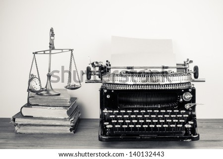 Vintage old typewriter, scales with watches and money, books on wood table