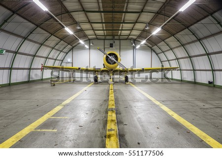 Vintage old yellow war plane inside of a clean empty hangar