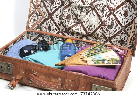Vintage open suitcase with clothes and summer and beach  items