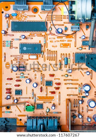 Vintage orange populated printed circuit board PCB showing the conductive traces vias the through-hole paths to the other surface and some mounted electrical components