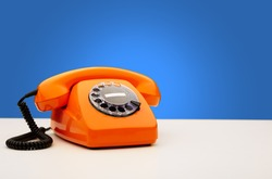 Vintage Orange Telephone On Blue Background