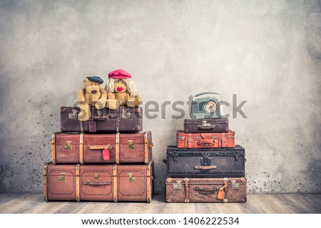 Vintage outdated trunks luggage, old antique leather valises,  pair of Teddy Bear toys and classic portable radio front concrete wall background. Retro style filtered photo