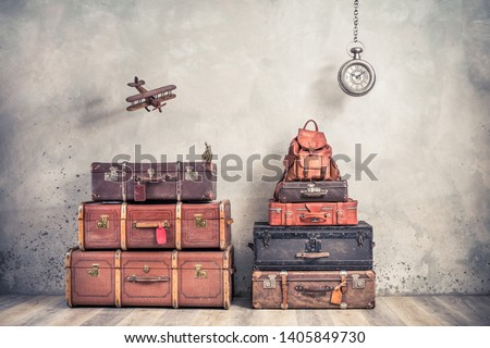 Vintage outdated trunks luggage, old antique valises, classic leather backpack, flying wooden toy plane and hanging big clock front concrete background. Travel by air concept. Retro style photo