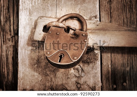 vintage padlock on old barn in sepia color - stock photo