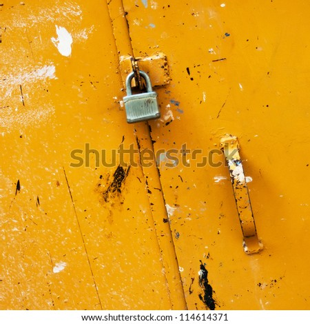 vintage padlock on old yellow barn