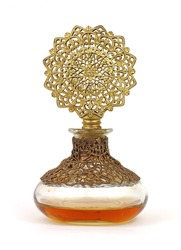 Vintage perfume bottle with gold filigree top and amber colored liquid.
