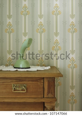 Vintage phone in front of patterned wallpaper