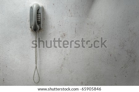 vintage phone mounted against a dirty wall