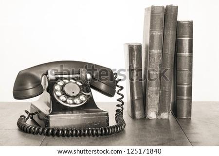 Vintage phone, old books on table sepia photo