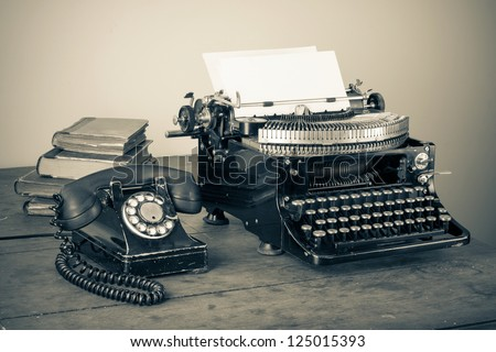 Vintage phone, old typewriter, books on table desaturated photo
