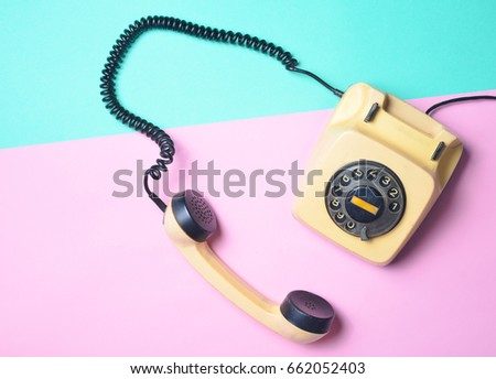 Vintage phone on a blue pink  pastel table. Pop colors. Communication 80s. Flat lay. #662052403