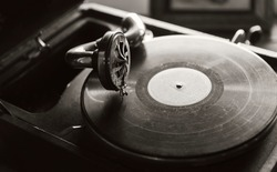 Vintage phonograph with black vinyl record plays an old music, sepia toned vintage stylized monochrome photo