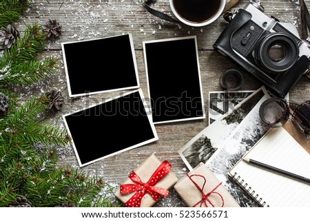 Vintage photo camera on christmas wooden background with blank photo frames, cup of coffee, notebook and gift boxes. top view. flat lay