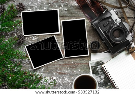 Vintage photo camera on christmas wooden background with blank photo frames, notebook and cup of coffee. top view. flat lay