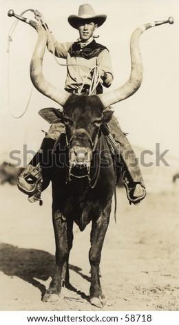 Vintage photo, circa 1900, of a cowboy riding a longhorn steer