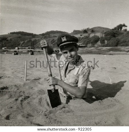 Vintage photo circa 1959 of a teenage boy half buried in the sand on the beach.Organic fading scratches, and artifacts.