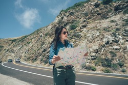 vintage photo female hiker pick up local paper map looking choosing travel destination at road trip on highway 1 california usa. confident girl backpacker in sunglasses walking on sunny day outdoor