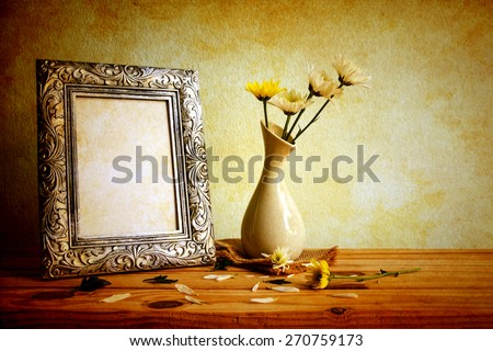 Vintage photo frame and flowers on wooden table over grunge background, Still life style