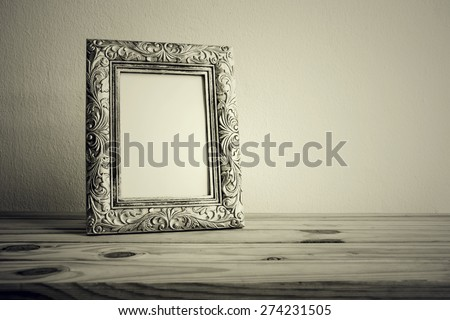 Vintage photo frame on wooden table over grunge background, Still life style