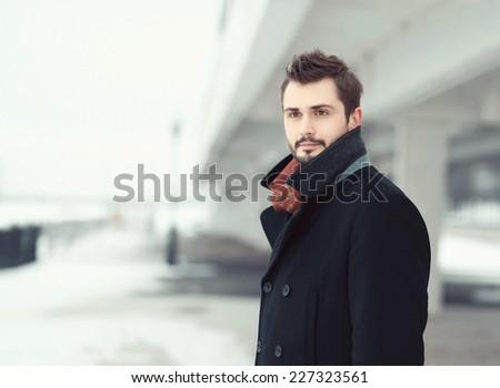 Vintage photo handsome stylish bearded brunette man in black coat looks away outdoors