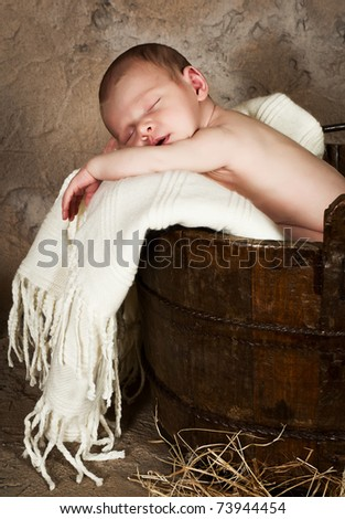 Vintage photo of a little baby of 18 days old sleeping in an antique bucket