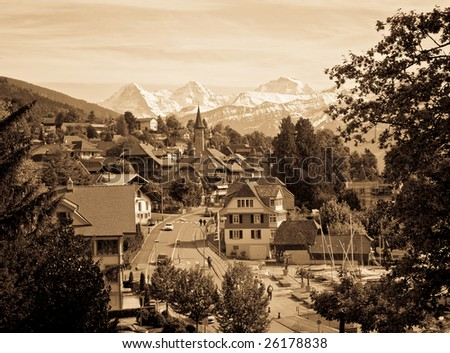 Vintage photo of a Swiss village with snowy peaks on the background