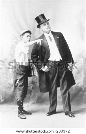 Vintage photo of a young boy giving directions to a man in a tuxedo
