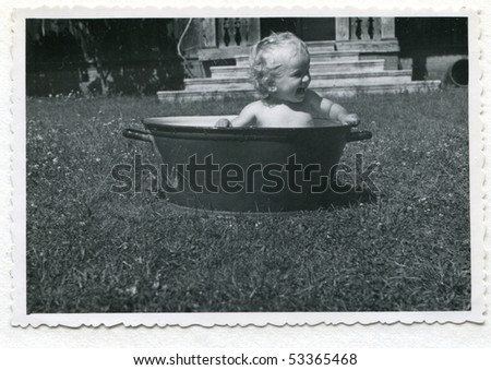 Vintage photo (1955) of baby taking a bath in a washtub