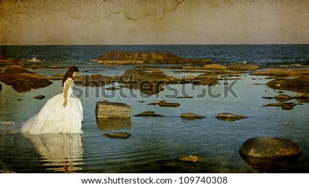 Vintage photo of beautiful bride standing on a cliff on the sea