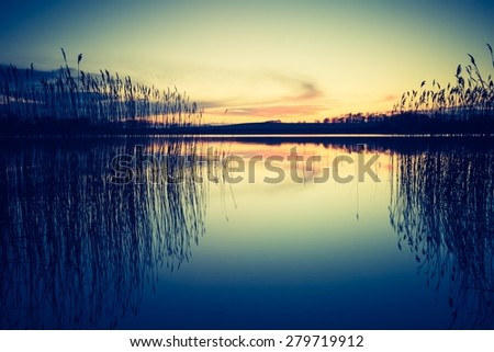 Vintage photo of beautiful sunset over calm lake.