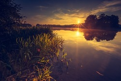 Vintage photo of beautiful sunset over calm lake. Landscape photographed in Mazury lake district.