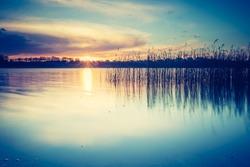 Vintage photo of beautiful sunset over calm lake. Mazury lake district landscape.