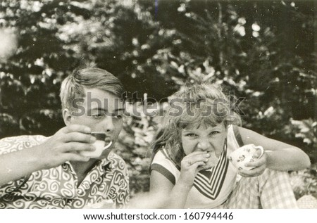 Vintage photo of brother and little sister eating outdoor - fifties