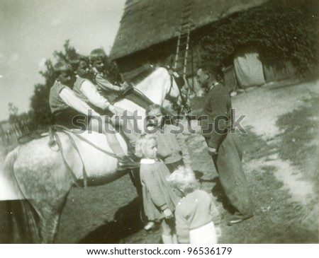 Vintage photo of children riding a horse in farm (fifties)