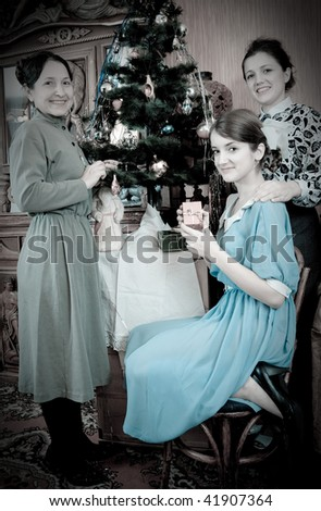 Vintage photo of  daughters with mother decorating Christmas tree at home