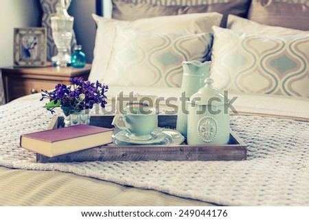 Vintage photo of decorative tray with book,tea set and flower on the bed