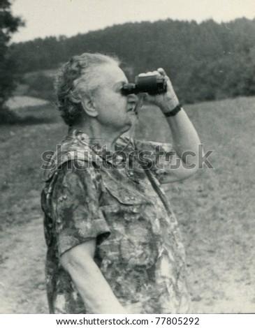 Vintage photo of elderly woman looking by binoculars (fifties)