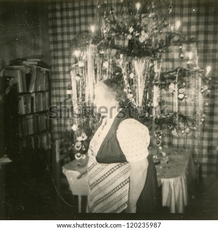 Vintage photo of elderly woman near Christmas tree (fifties)