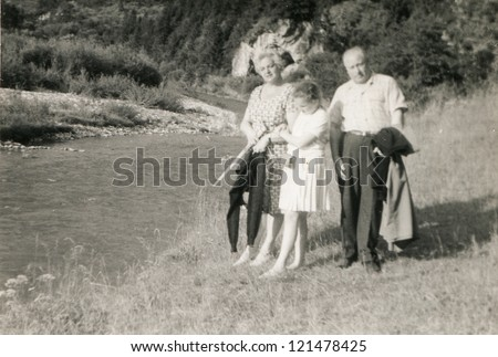 Vintage photo of family (grand father, mother and daughter) walking at riverside (sixties)