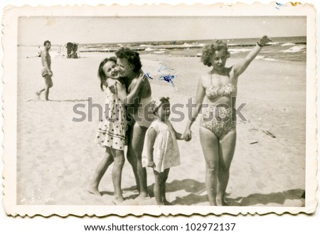 Vintage photo of family on beach (fifties) - stock photo